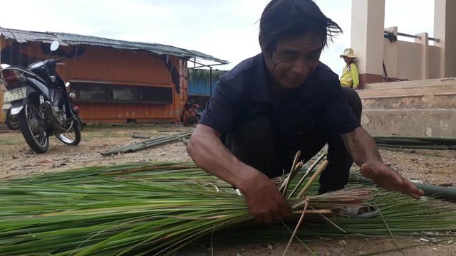 Ông Hồ Văn Lâm dành 2 ngày vào rừng cắt tranh về lợp lại mái nhà bán trú container giúp nhà trường.