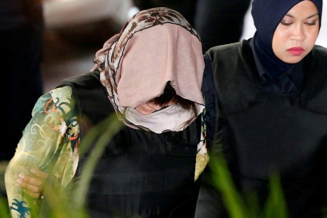 Các bị cáo được mặc áo chống đạn và đeo khăn trùm đầu khi bị lực lượng an ninh áp giải tới phiên tòa. (Ảnh: Reuters)