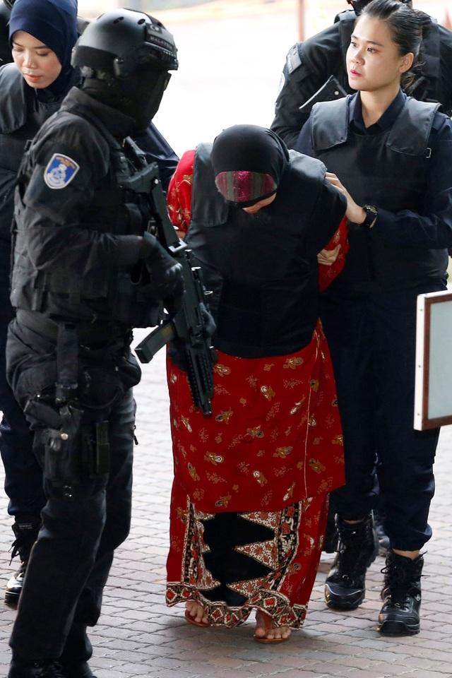 Cảnh sát Malaysia được trang bị súng khi áp giải các bị cáo và bảo đảm an ninh bên ngoài khu vực xử án. Trong ảnh: Bị cáo Siti Aisyah được đưa tới tòa Shah Alam. (Ảnh: Reuters)