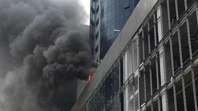 Đám cháy bùng phát từ khu vực bảng điện trong tòa nhà, cột khói bốc cao hàng chục mét khiến nhiều người hoảng loạn (Ảnh: Thắng Nhân).