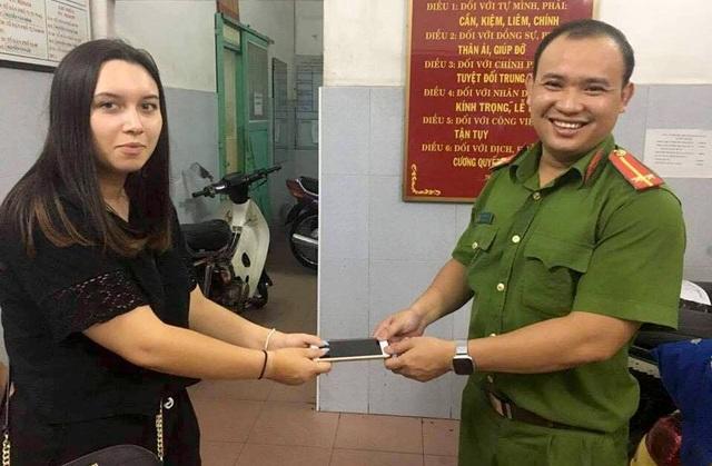 Đại diện công an trao trả chiếc điện thoại cho nữ du khách