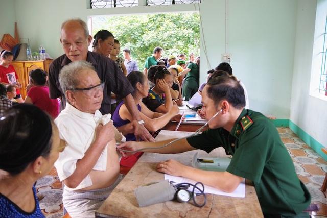 Quân y BĐBP hướng dẫn người dân cách sử dụng thuốc chữa bệnh. (Ảnh: Lê Thạch)