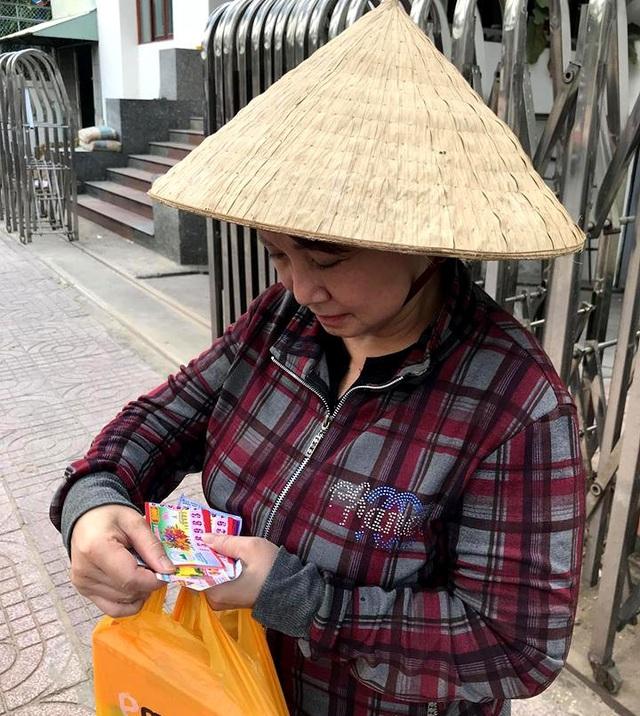 Bà Phượng với xấp vé số trên tay đi bán trên hè phố Sài Gòn.