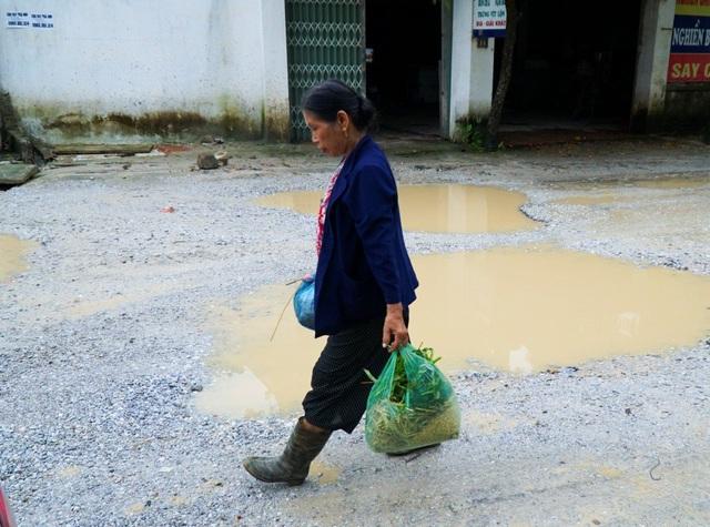Mỗi khi trời mưa, bà Quý (67 tuổi, đường Hoàng Hoa Thám, Hà Ninh) phải đi ủng để vượt qua đoạn đường lầy lội.