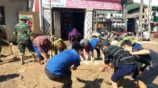 Các đoàn viên giúp dân nạo vét bùn để sớm ổn định cuộc sống.