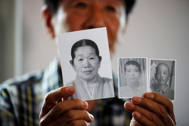 Một người đàn ông Hàn Quốc chìa bức ảnh của người mẹ quá cố và hai người em ruột đang sống ở Triều Tiên. (Ảnh: Reuters)