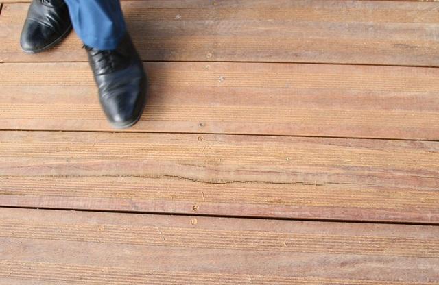 Một vết nứt dài ở tấm gỗ lim đã được lát trên đường đi bộ ven sông Hương