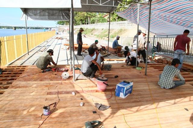 Các công nhân đang tiến hành lát gỗ lim dưới tiết trời nắng nóng
