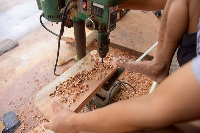 Để giảm thời gian đục khuôn, ông dùng máy khoan thành nhiều lỗ trên bản gỗ.