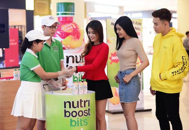 Nhiều bạn trẻ khá thích thú khi vừa được thưởng thức sữa trái cây Nutriboost đào miếng vừa được đóng một chiếc mộc xinh xắn trên tay