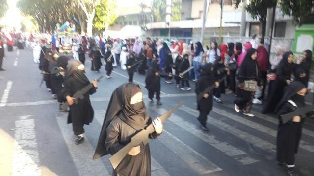 Các em nhỏ mặc quần áo đen mang súng diễu hành ở Indonesia (Ảnh: Twitter)
