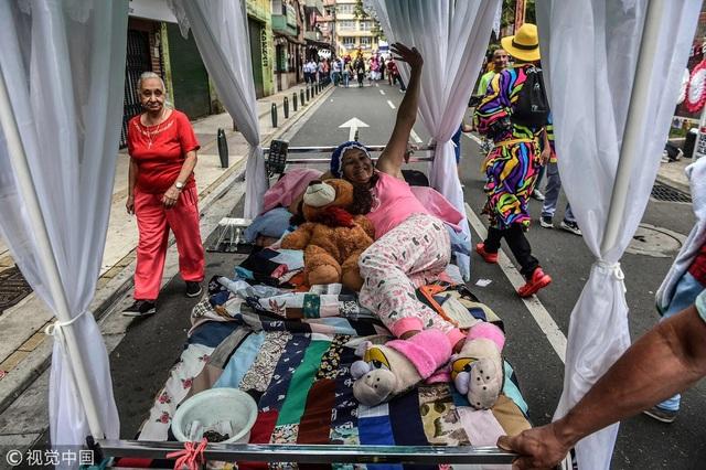 Một người phụ nữ mang theo chiếc giường nhiều thú bông, vui vẻ vẫy tay chào khi được chụp hình