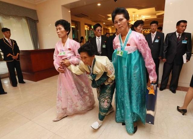 Những phụ nữ Triều Tiên cao tuổi mặc những bộ trang phục truyền thống hanbok với màu sắc rực rỡ, run rẩy bước đi với sự hỗ trợ của các thân nhân.
