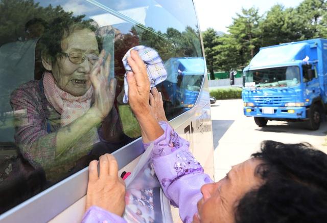 """""""Đừng khóc, tạm biệt các con"""", bà Han Shin-ja, 99 tuổi, nói trong nước mắt khi nhìn hai con gái qua cửa kính xe buýt. Hai con gái của bà, lần lượt 72 và 71 tuổi, cũng bật khóc trong khoảnh khắc chia tay mẹ."""