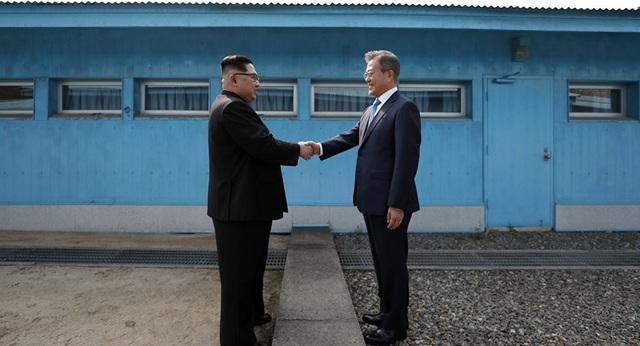 Tổng thống Hàn Quốc Moon Jae-in và nhà lãnh đạo Triều Tiên Kim Jong-un bắt tay nhau tại biên giới liên Triều hôm 27/4. (Ảnh: AFP)