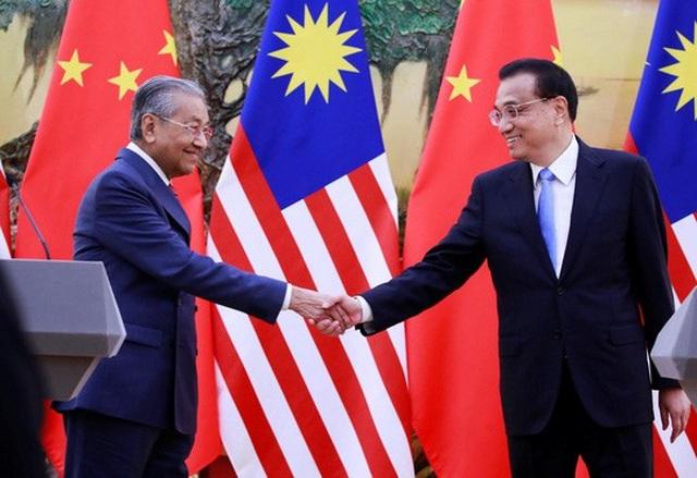 Thủ tướng Malaysia Mahathir Mohamad (trái) bắt tay với người đồng cấp Trung Quốc Lý Khắc Cường sau cuộc họp báo tại Bắc Kinh hôm 20-8 Ảnh: REUTERS
