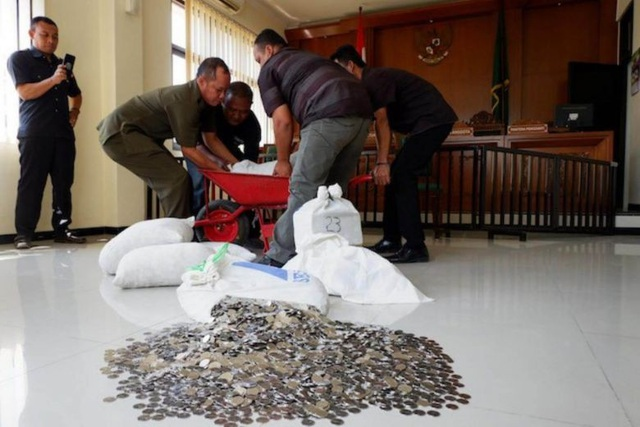 Ông Dwi Susilarto và 2 người bạn khiêng các bao tải tiền xu tới phòng xử án bồi thường cho vợ cũ. (Ảnh: Jakarta Post)