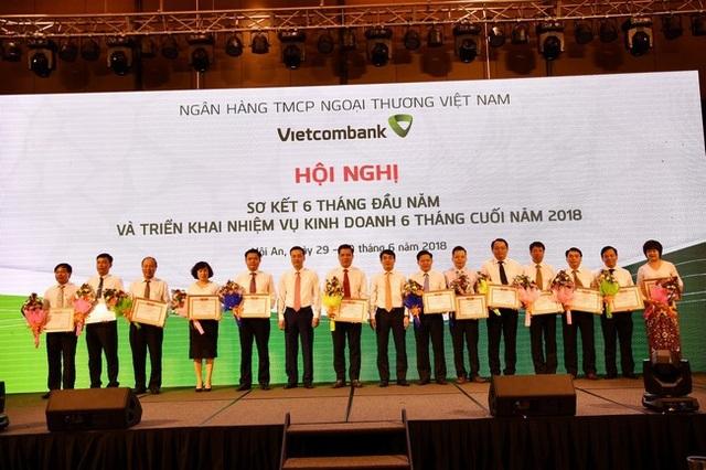Chủ tịch HĐQT Nghiêm Xuân Thành (thứ 8 từ phải sang) và Tổng giám đốc Phạm Quang Dũng (thứ 6 từ trái sang) tặng Giấy khen và hoa cho 13 chi nhánh tiêu biểu trên một số mặt hoạt động 6 tháng đầu năm 2018