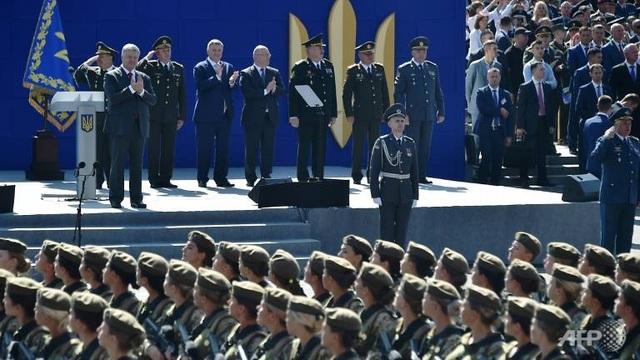 """Phát biểu tại lễ duyệt binh, Thủ tướng Ukraine Petro Poroshenko nói: """"Chúng ta cúi đầu trước mỗi gia đình Ukraine đã mất chồng, mất con trai, mất mẹ và chị em gái. Mãi mãi tưởng nhớ tới những anh hùng đã ngã xuống vì sự tự do, nền độc lập của Ukraine"""". (Ảnh: AFP)"""