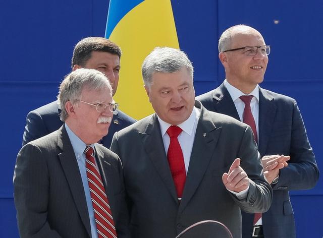 Lễ duyệt binh còn có sự góp mặt của Cố vấn An ninh quốc gia Mỹ John Bolton (bên trái). Trong ảnh: Ông Bolton đang trao đổi với ông Poroshenko. (Ảnh: Reuters)