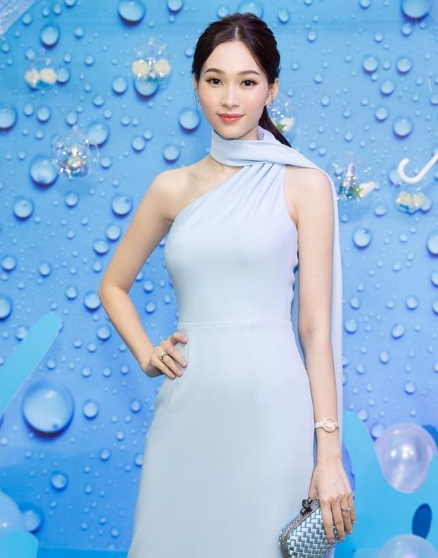 Chiếc đầm cao cổ, khoe phần vai gầy trắng nõn nà và có phần vải buông nhẹ nhàng sau vai càng khiến cho vóc dáng của cô thanh thoát và không kém phần thanh lịch, sang trọng.