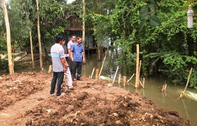 Ông Phan Văn Sương - Chủ tịch UBND huyện Tri Tôn (áo xanh) đến kiểm tra thực địa miệng cống vừa được vá lại sau sự cố bị vỡ vào 15h chiều ngày 25/8