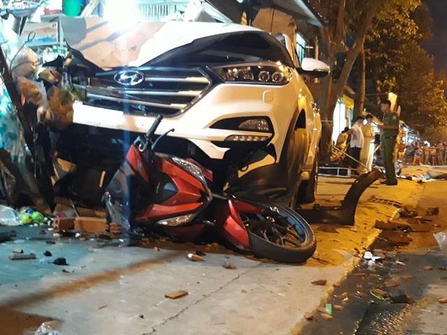 Một xe máy mắc kẹt dưới gầm xe ô tô.