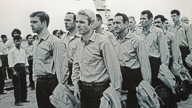 Sau khi Hiệp định Paris được ký kết, năm 1973, ông Joh McCain (giữa) và nhiều tù nhân chiến tranh Mỹ khác được trao trả. Trong ảnh, John McCain trên đường tới sân bay Gia Lâm (Hà Nội) để quay về Mỹ.