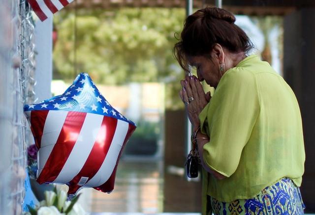 Một người dân ở Phoenix, Arizona, đặt hoa tưởng niệm bên ngoài văn phòng làm việc của ông McCain.