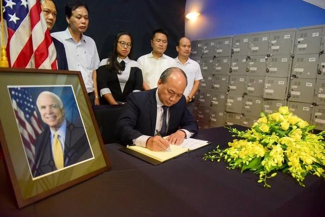 Thứ trưởng Bộ Nông nghiệp và Phát triển nông thôn Vũ Văn Tám ghi sổ tang tưởng nhớ ông McCain.