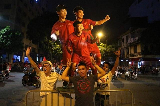 Hình các cầu thủ Olympic Việt Nam bằng giấy được mang theo ăn mừng.