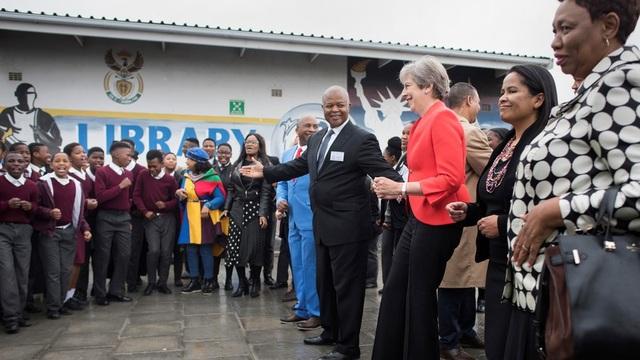 Thủ tương Anh Theresa May nhún nhảy vui vẻ cùng trẻ em Nam Phi (Ảnh: Reuters)