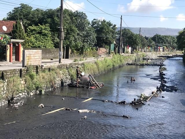"""Vào mùa mưa, nước cuốn theo dòng than trên các khai trường đổ xuống suối trở thành """"phù sa"""" nuôi sống không ít người."""