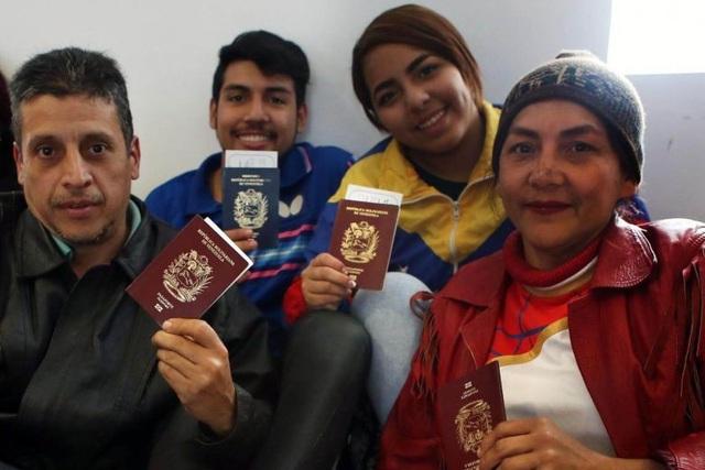 Những người Venezuela tị nạn cầm trên tay hộ chiếu và vé máy bay chuẩn bị hồi hương (Ảnh: AFP)