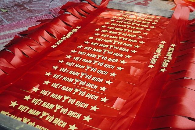 """Theo anh Phục, những ngày này, nhà xưởng phải dừng mọi hoạt động sản xuất các sản phẩm khác để tập trung làm các sản phẩm cổ động bóng đá. Ngoài cờ Tổ quốc còn có các băng rôn in hình: """"Việt Nam vô địch"""". Do nhu cầu lớn nên xưởng sản xuất của anh Phục luôn trong tình trạng tất bật ngày đêm."""