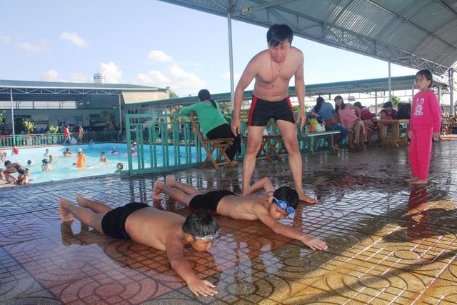 Các anh chị đoàn viên đang hướng dẫn bơi cho các em học sinh vùng cao.