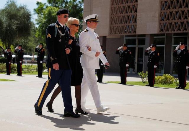 Bà Cindy McCain, phu nhân cố Thượng nghị sĩ John McCain, cùng hai con trai James (trái) và John (phải) đi theo sau linh cữu tiến vào tòa nhà nghị viện Arizona.