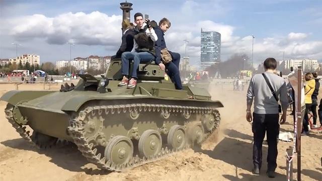 Các nạn nhân ngồi trên xe tăng trước khi ngã xuống và bị xe chèn qua người (Ảnh: Ruptly)