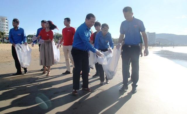 Phó Chủ tịch UBND tỉnh Bình Định Nguyễn Phi Long (trái) tham gia nhặt rác làm sạch bãi biển Quy Nhơn.