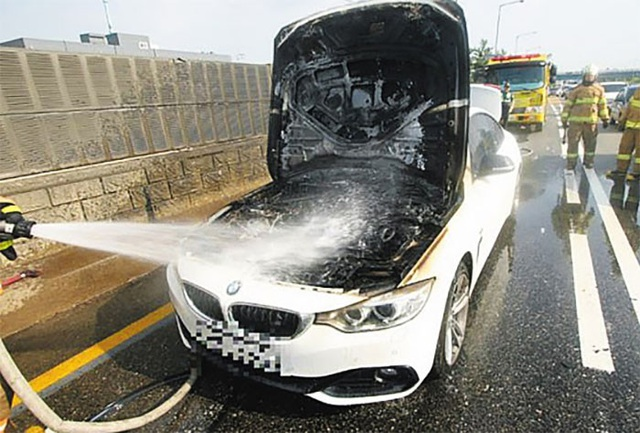 Lực lượng cứu hỏa nỗ lực dập lửa phát ra từ khoang động cơ của một chiếc BMW 420d trên một đường cao tốc ở Incheon hôm 31/7.
