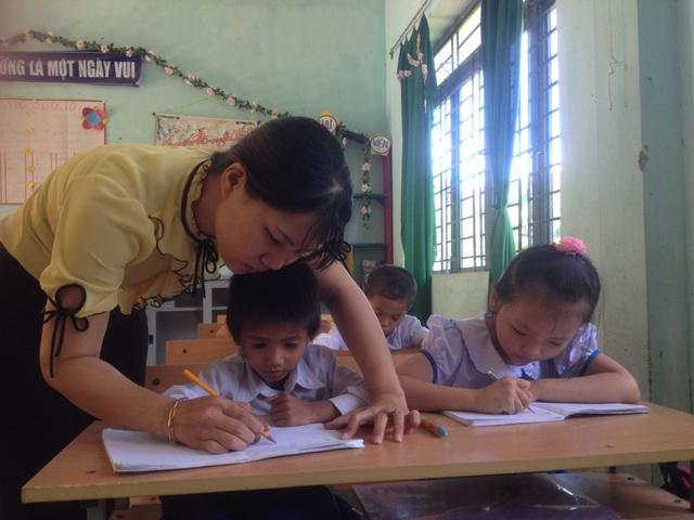 Giáo viên huyện Sơn Tây (Quảng Ngãi) hướng dẫn cho học sinh tập tô chữ cái tiếng Việt.