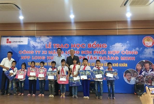 Lãnh đạo công ty xi măng Long Sơn và Hội Khuyến học Thanh Hóa trao học bổng cho các em học sinh.