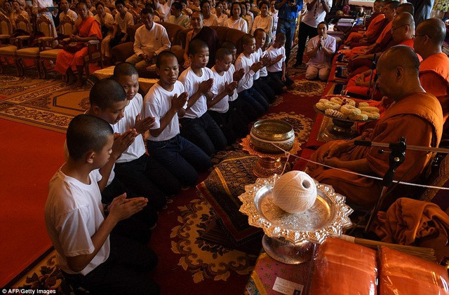 Các thành viên trong đội bóng đã cùng cúi đầu cầu khấn khi các nhà sư làm lễ trong chùa. (Ảnh: AFP)