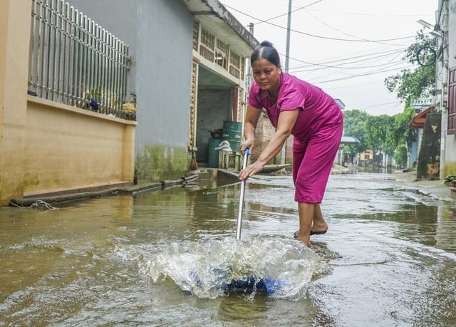 """Trên đường làng thôn Cấn Hạ, có những đoạn nước đã rút hết. Bà Lan (61 tuổi) cho biết: """"Nước bắt đầu rút mạnh từ ngày 4/8, tuy nhiên, hệ quả tai hại chắc phải nhiều tuần nữa mới giải quyết xong."""