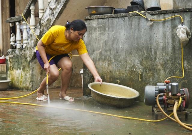 Sau nửa tháng ngập trong nước, việc cần làm ngay của gia đình chị Thanh ở thôn Đĩnh Tú là rửa rọn nhà cửa, sân vườn. Rác và rêu có mặt ở khắp nơi.