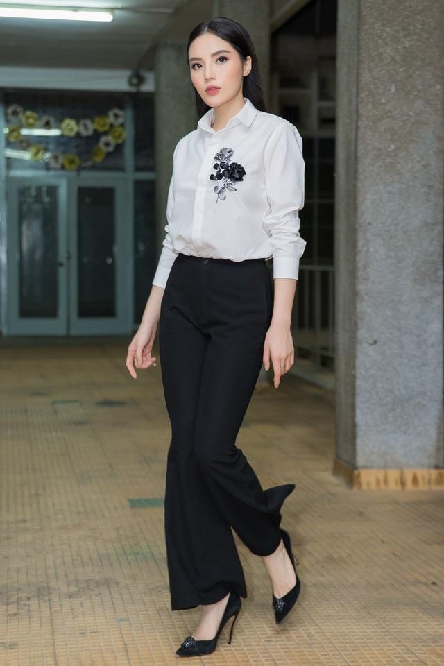 Kỳ Duyên lựa chọn áo sơ mi trắng thêu hoa thanh lịch, mix cùng quần tây ống loe mang đến sự gần gũi.