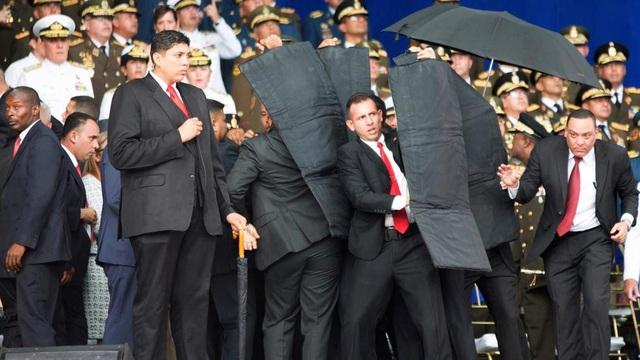 Các vệ sĩ nhanh chóng lập hàng rào che chắn cho Tổng thống Maduro. (Ảnh: Getty)