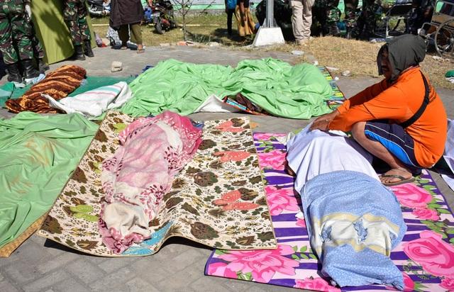 Một người đàn ông ngồi cạnh thi thể của những người thân thiệt mạng sau trận động đất tại Indonesia.
