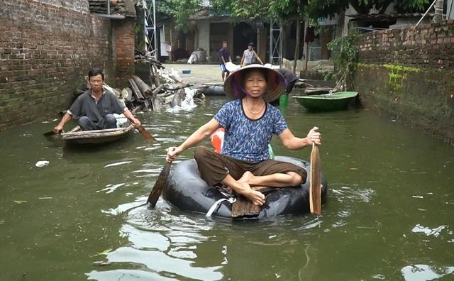 Hơn nửa tháng trôi qua, làng Nam Hài (xã Nam Phương Tiến, Quốc Oai) vẫn ngập chìm trong nước. Nhiều người dân chèo thuyền đi nhận quà từ thiện.