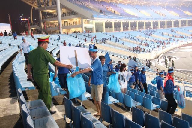 Ảnh 3: Một cán bộ giữ gìn an ninh trật tự cho trận đấu cũng tham gia vào dọn rác sau trận đấu.